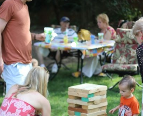 People playing giant Jenga at a family BBQ