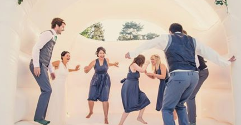 Wedding party jumping in a white bouncy castle