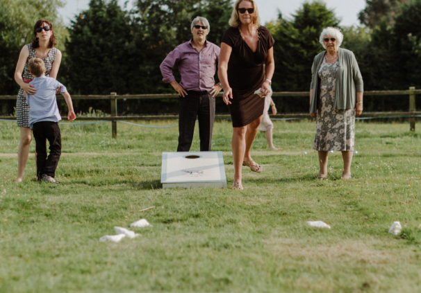 Family in the backyard playing cornhole toss