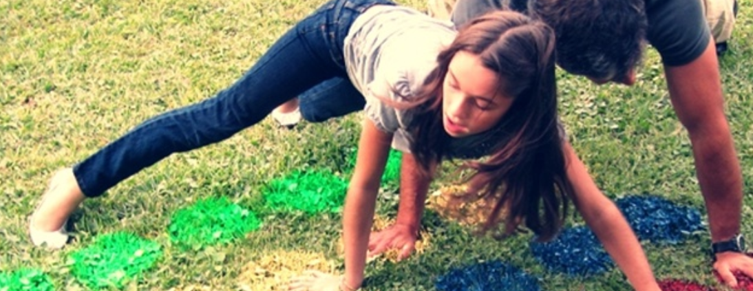 2 people playing twister on grass with spray painted coloured circles